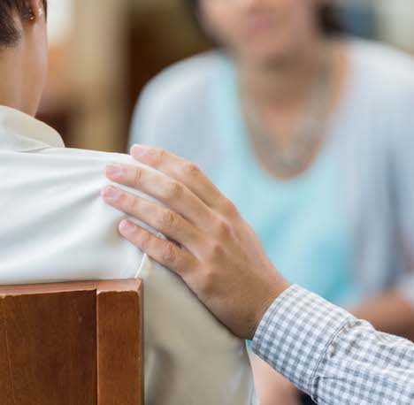 Man comforts woman during counseling session