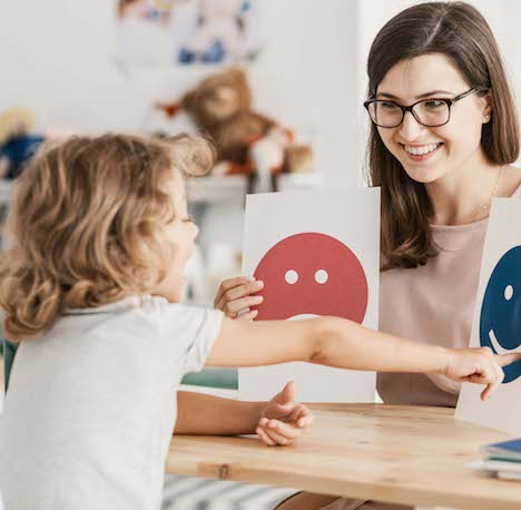 Psychologist and child during a therapy session with a child. Showing emotion pictures